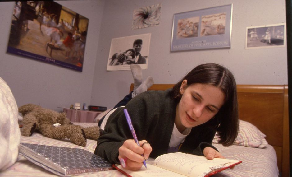 RJ file photo - Teen playwright Erica Magrey of Southington writes in several notesbooks with multi-colored pens, March 1994.