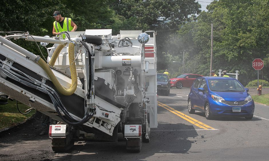 FILE PHOTO – A worker for Waterbury based Connecticut Sealcoating operates a milling machine around Dutton Park at Cedar Lane and North Main Street in Wallingford, Mon., July 29, 2019. Work began Monday on a road milling and paving project that covers the entire lengths of both North Main and South Elm streets. Dave Zajac, Record-Journal