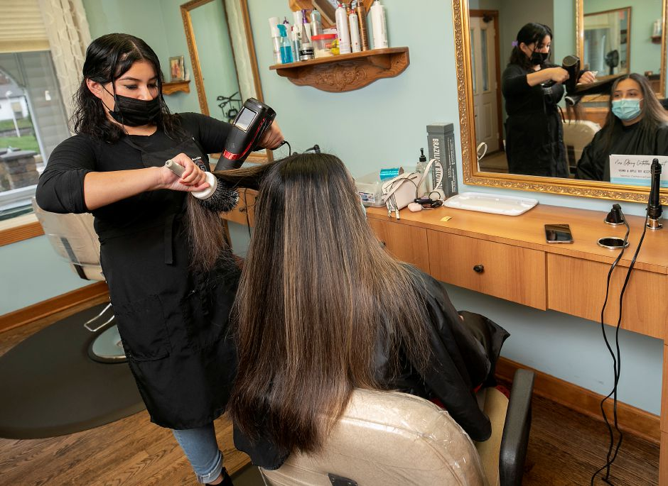 Stylist Jailene Ruiz, of Southington, guides a brush and blow dryer on the hair of customer Kimberly Tapia, of Wallingford, on Friday.