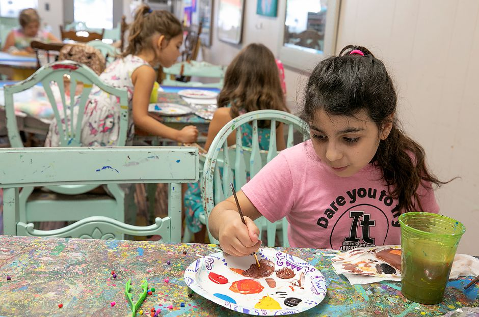 Gianna Martone, 8, of Cheshire, freshens a brush with brown paint while working on her owl during an art camp at Catalyst Art Studio, 88 Center St., Wallingford, on Thursday.
