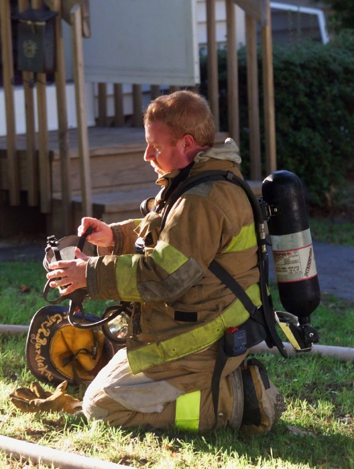 Meriden Fire Dept. Capt. Robert Burdick outside of a Yale Acres home Thurs., Oct. 7 1999 after fighting a smokey fire. He was changing his air pack.