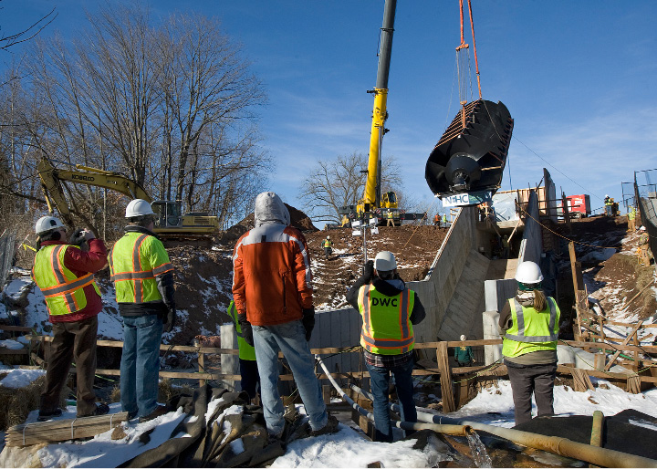 Construction crews and city officials watch as a 20-ton, 35-foot-long metal screw is lowered into place by crane at Hanover Dam in South Meriden, Tuesday, December 20, 2016. The Archimedes screw, named for the ancient Greek scientist credited with its invention, is the first of its kind installed in the U.S.  | Dave Zajac, Record-Journal