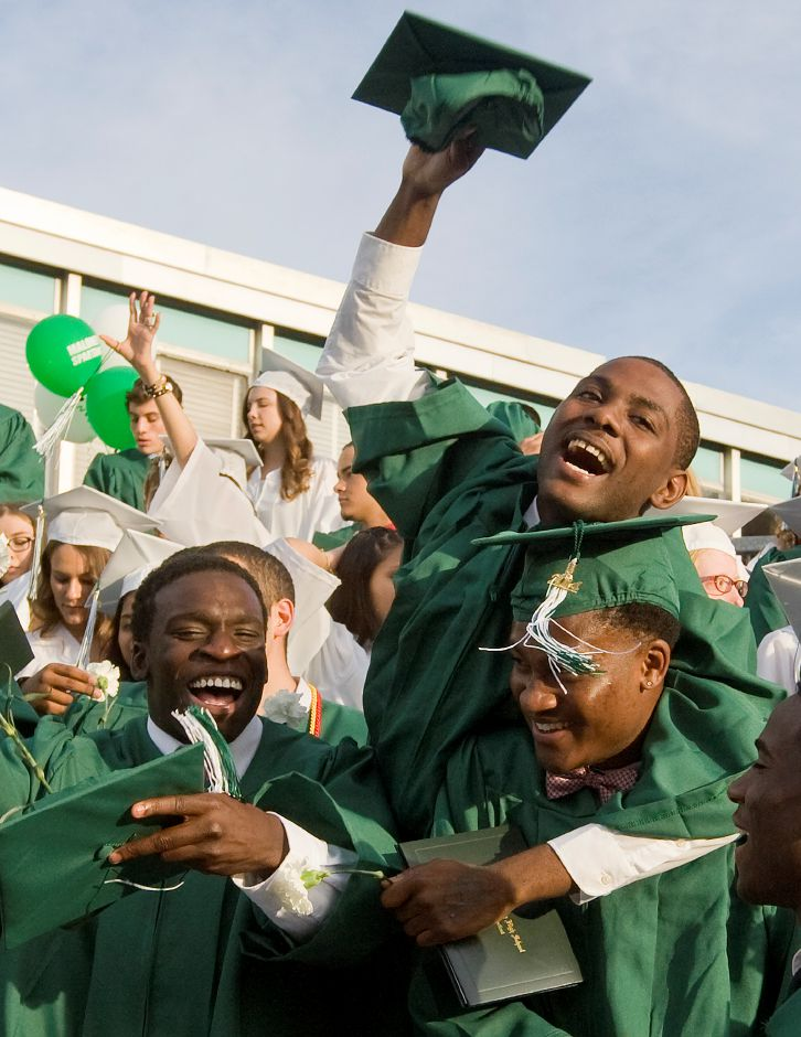 Graduate Nasir Reaves, top, celebrates with friends, Dimitri Smith, left, and Donte Smith at the conclusion of commencement at Maloney High School, Friday, June 20, 2014. | Dave Zajac / Record-Journal