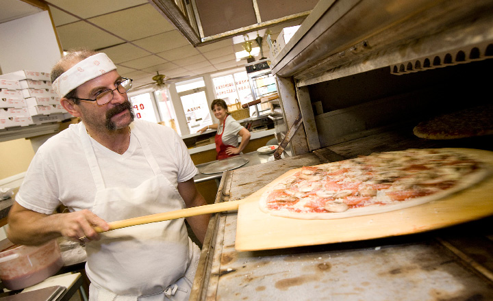 With wife Diane watching, Ken Minervini works on a pizza Friday at the couple's restaurant in Wallingford.  | Dave Zajac, Record-Journal