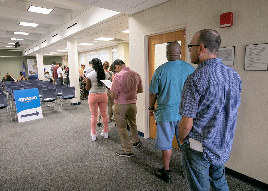 Job candidates wait in line to talk with Amazon representatives during a hiring event at the Wallingford Public Library, Wed., July 17, 2019. Dozens of people attended the Amazon hiring event held in the Community Room and lobby of the library. Dave Zajac, Record-Journal