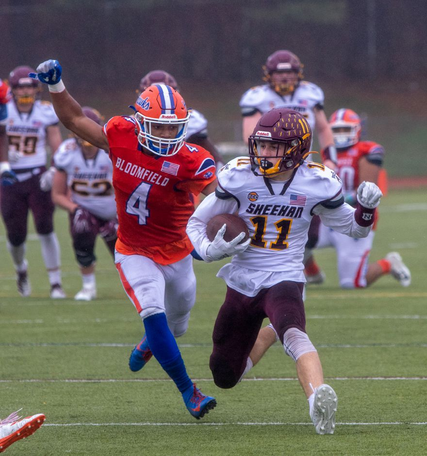 The Titans'  Michael Lemay is chased down by Bloomfield's William Moore during the first half of Saturday's game. Aaron Flaum, Record-Journal