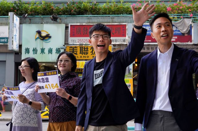 Election winner candidate Kelvin Lam, right, and pro-democracy activist Joshua Wong, second right, wave to people and thank for their support, outside South Horizons Station in Hong Kong, Monday, Nov. 25, 2019. Pro-democracy candidates won nearly half of the seats in Hong Kong