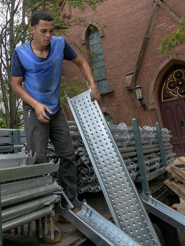 Joshua Fernandez, a worker for Rocky Hill based Enterprise Scaffolding, Inc., loads scaffolding on a flatbed truck while working in hot and humid conditions at The First Congregational Church in Wallingford on Wednesday.