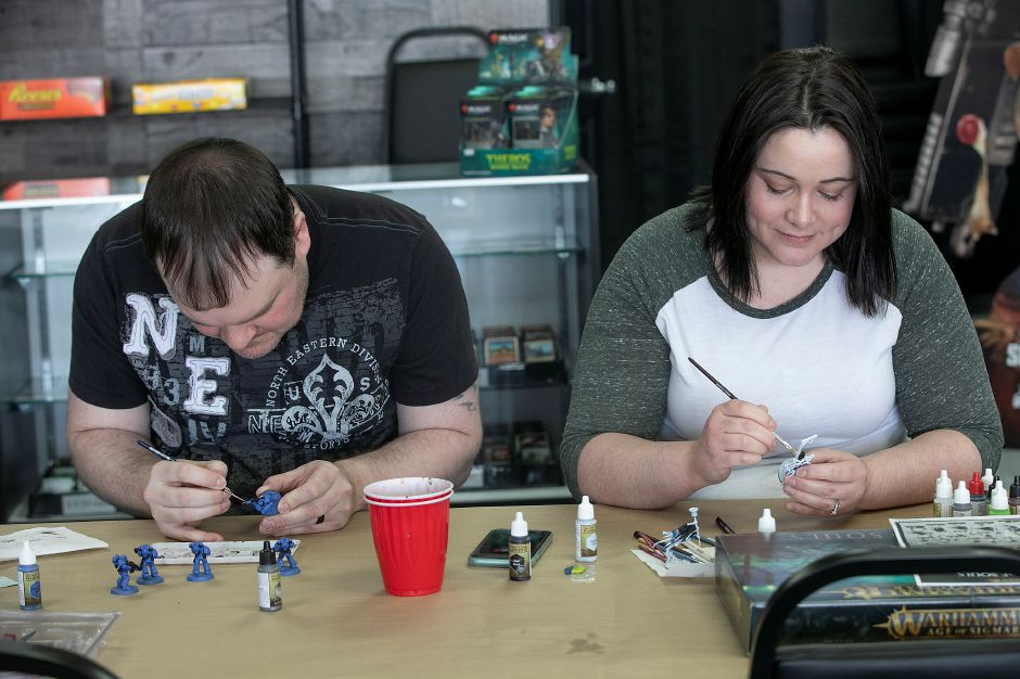 Eric and Christina DeVeau paint miniature figures at the new business on Wednesday.