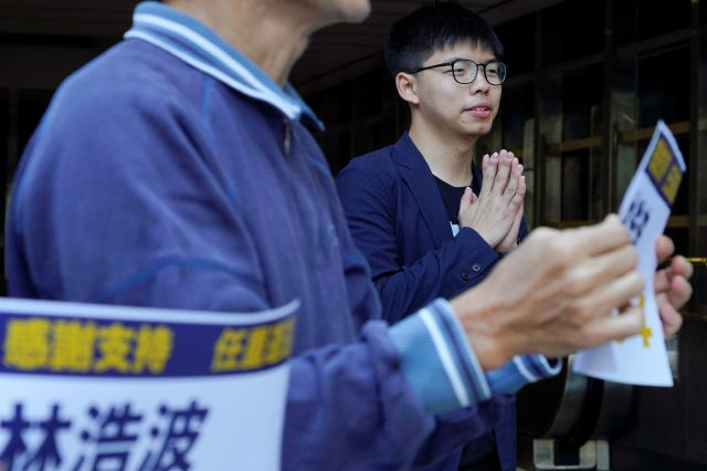 Pro-democracy activist Joshua Wong, right, gestures, as election winner candidate Kelvin Lam greets people to thank for their support, outside South Horizons Station in Hong Kong, Monday, Nov. 25, 2019. Pro-democracy candidates won nearly half of the seats in Hong Kong