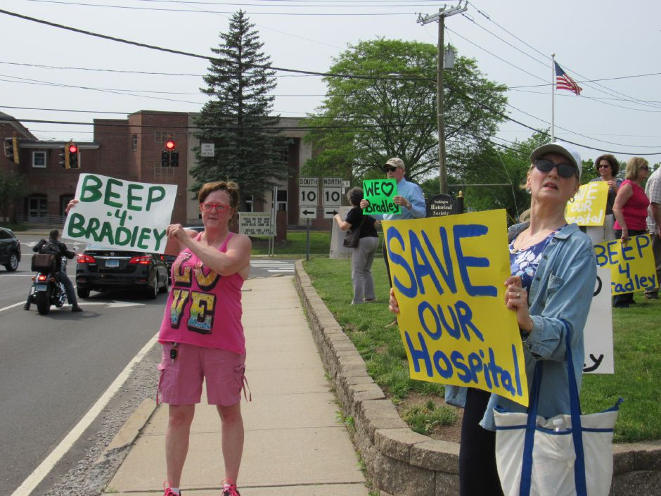Michelle Dozier (left) and Cheryl Pasek hold signs for the Community Committee to Save Bradley in a rally in front of the Southington Historical Society, Saturday, June. 1, 2019. | Jeniece Roman, Record-Journal.