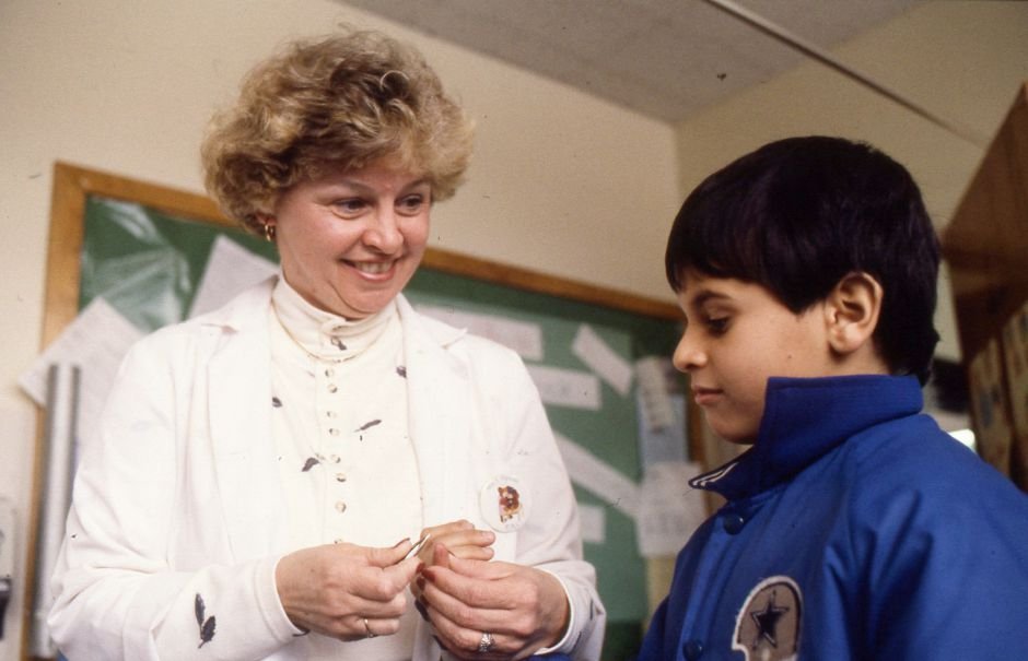 RJ file photo - Nurse Judy Pipicelli removes a splinter from the hand of 4th-grader Omar Marquez at Nathan Hale School in Meriden Jan. 24, 1990.