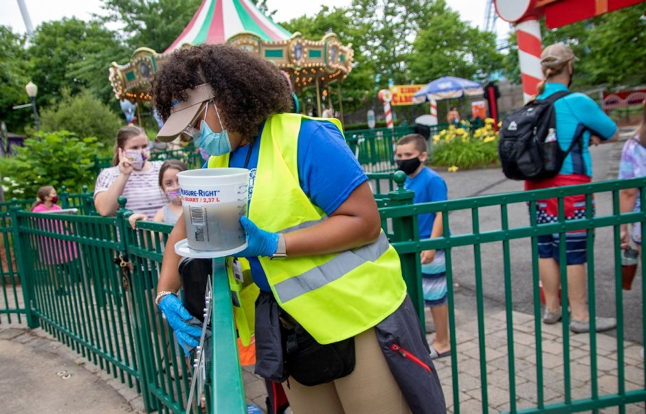 Christy Martinez a member of the Lake Compounce cleaning crew, works on wiping down the railings around the Kiddie Carousel as she makes her rounds through the kids' section of the park. Cleaning crew members wipe down high-touched surfaces and rides throughout the day. Aaron Flaum, Record-Journal