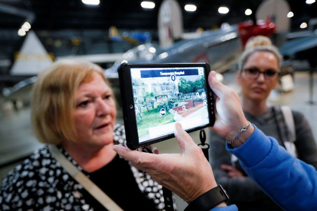 In this Friday, April 26, 2019 photo, Deane Sager, of Louisville, off camera, and his wife Cathy, left, use a Histopad tablet to view scenes from operations on the western front of World War II at the The National Museum of the U.S. Air Force, in Dayton, Ohio. French-developed technology making its U.S. debut this month will allow new views of the D-Day invasion 75 years ago that began the liberation of France and helped end World War II. The National Museum of the U.S. Air Force near...