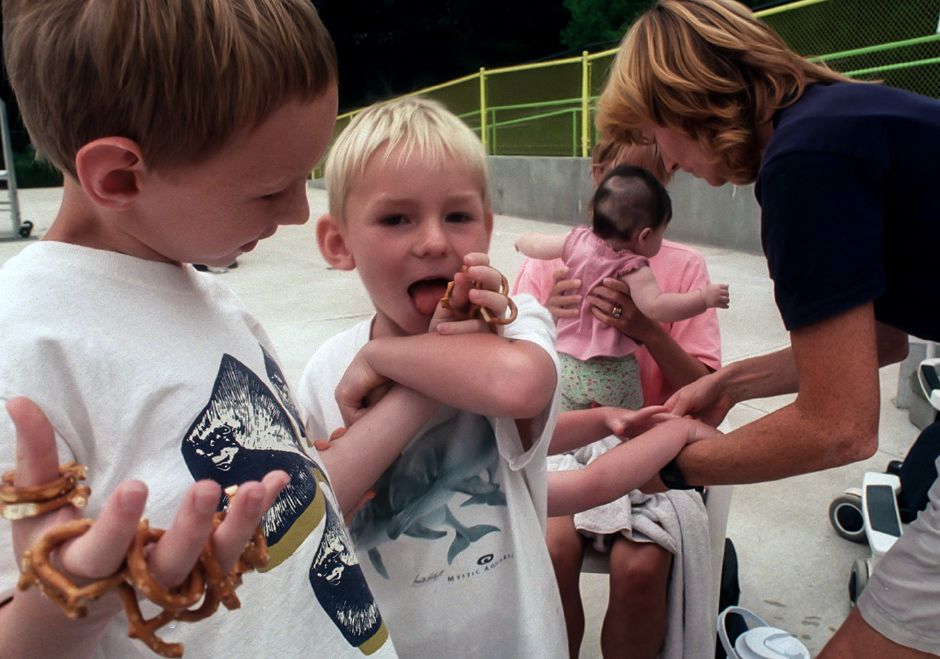 Matthew Comrie, 9, left, feeds pretzels off of his fingers to his brother Mason Comrie, 5, while their mother Sally Comrie is busy tending to their younger brother Michael Comrie, July 26, 2000. Joanne Russel holds her new daughter Hannah Russel of 4 months.