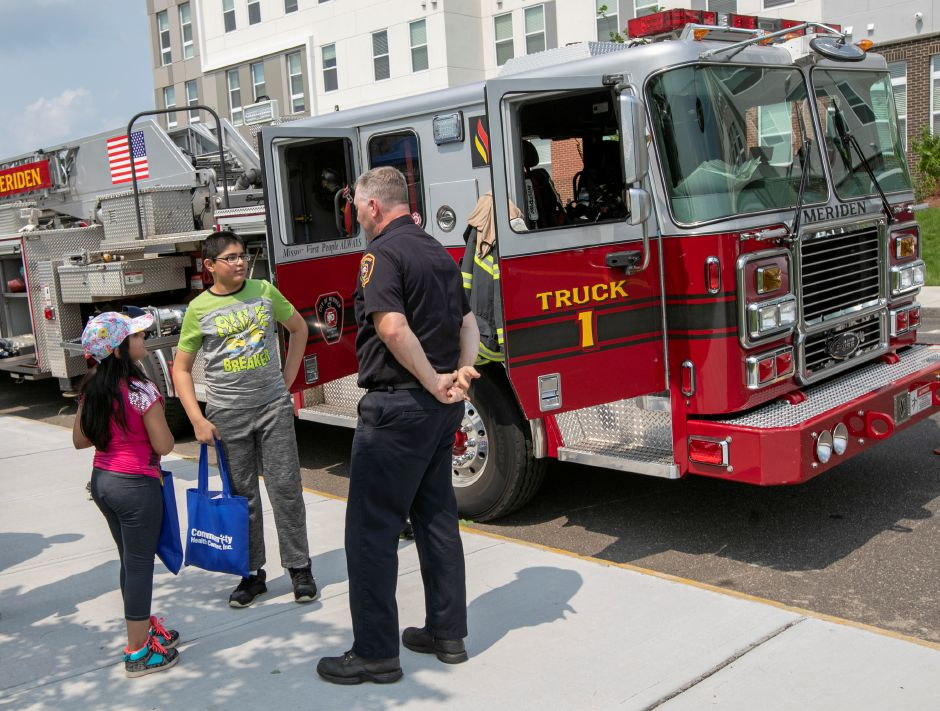 Meriden firefighter Dennis Campbell, talks with Nebraas Sattar, 12, and sister, Naveera, 8, of Meriden, during Community Health Center's health fair on the Meriden Green, Thursday, August 16, 2018. Community Health Center, Inc. is celebrating National Health Center week with a series of fairs around the state, including Meriden's event. Dave Zajac, Record-Journal