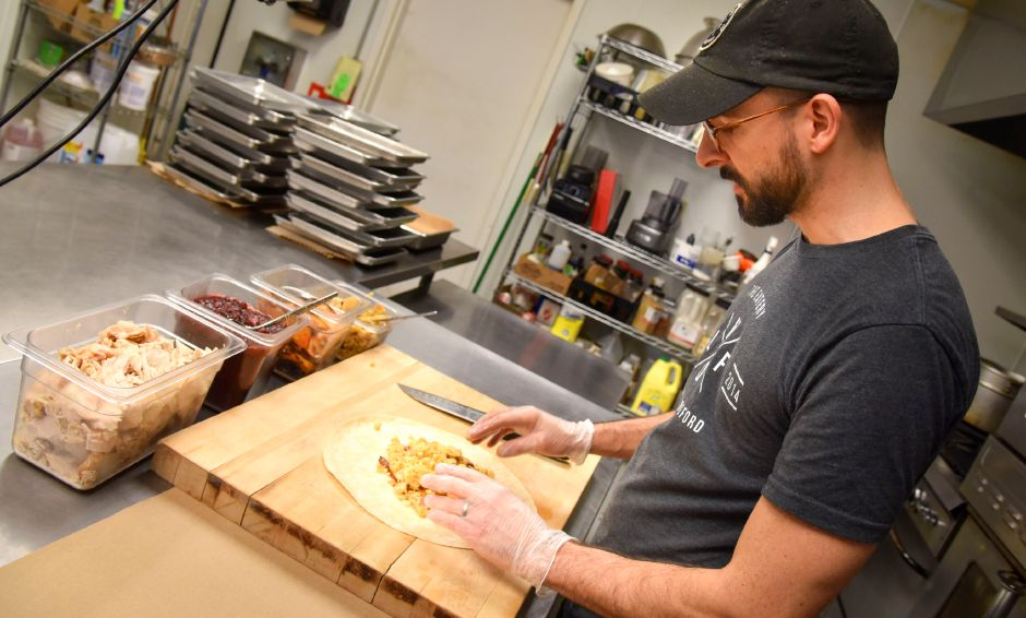 "The Eatery co-owner Jon Masella puts together the ""Mayflower Wrap"" with house-roasted turkey breast, maple roasted sweet potatoes, apple-cornbread stuffing, and pear cranberry sauce at the 65 S. Colony Road business in Wallingford on Nov. 21, 2019. It is one of the local restaurants that are still offering  take-out, delivery and curbside services in the midst of the coronavirus pandemic.Bailey Wright, Record-Journal  file photo"
