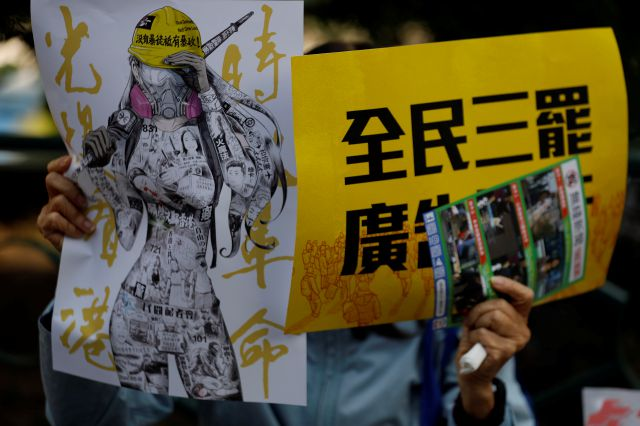 "An anti-government supporter holds up banners during a rally by the advertising industry in Hong Kong on Monday, Dec. 2, 2019. Several hundred people who work in advertising in Hong Kong say they will strike this week to support the anti-government protests in the semi-autonomous Chinese territory. The banner, right, read ""Advertising Industry joins all citizens three boycotts."" (AP Photo/Vincent Thian)"