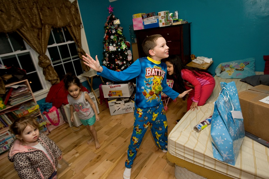 Angel Vazquez, 8, dances with excitement as Beat the Street Community Center delivers presents to his family