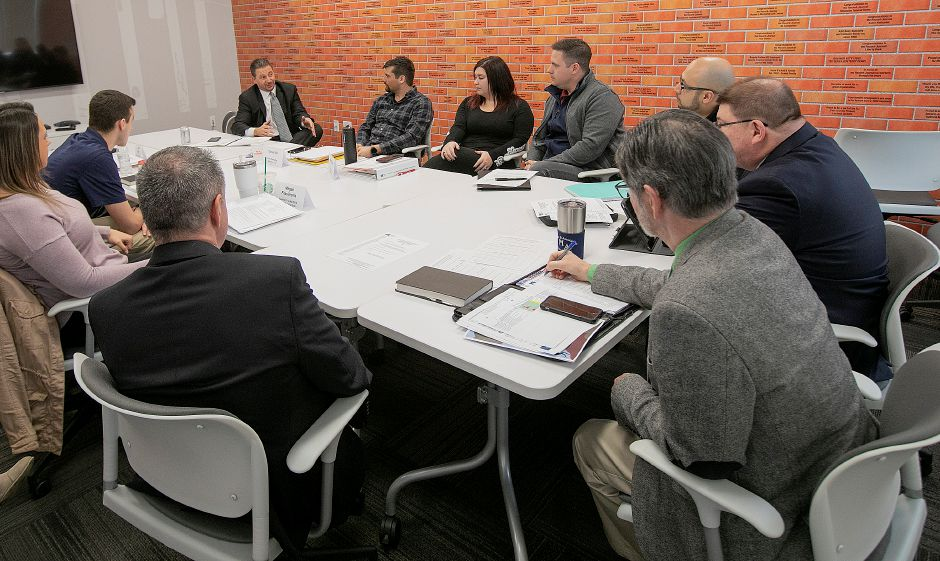 Midstate Chamber of Commerce President Sean Moore, right, makes a note as Dr. Mark Benigni, superintendent Meriden public schools, top left, speaks during a Leadership Academy of Meriden and Wallingford meeting at the Record-Journal, Fri., Mar. 15, 2019. Dave Zajac, Record-Journal
