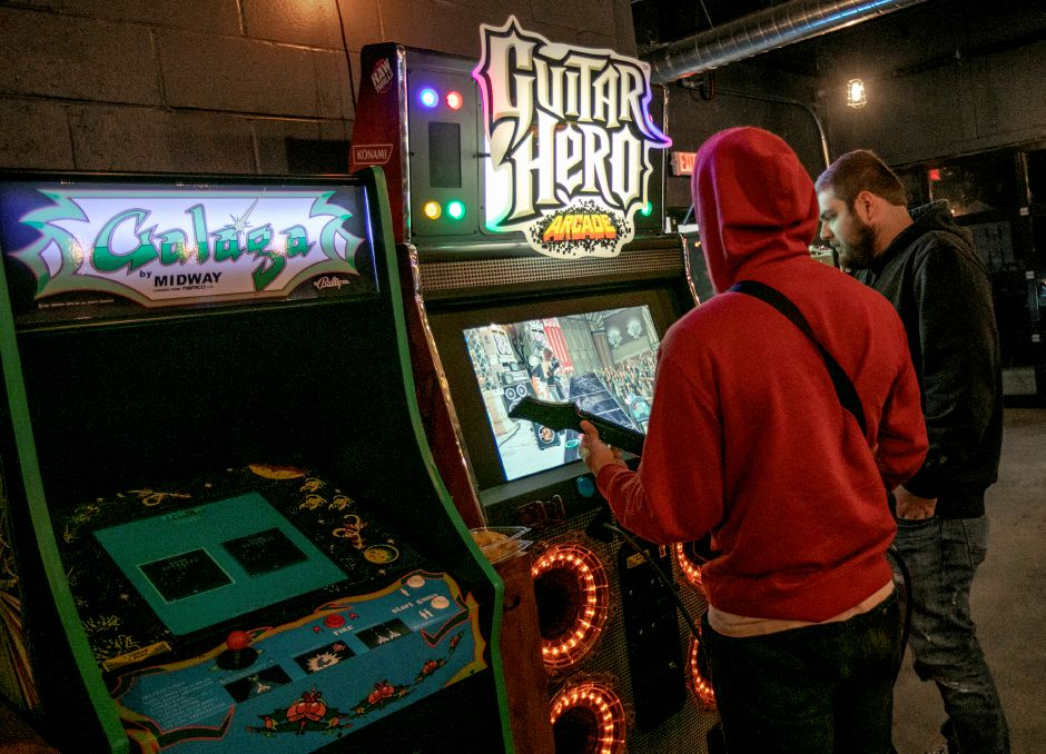 Krysten Morillo, left, and Jacob Rodrigues, both of Terryville, play Guitar Hero at GameCraft Arcade and Bar in the Factory Square building in Southington, Wed., Jan. 8, 2020. The new business features retro arcade games and a bar with local beers and cocktails. Dave Zajac, Record-Journal