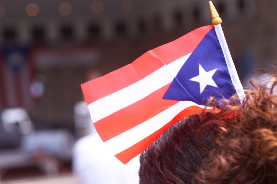 Linette Cruz ( cq),18 keeps her hair in place with a miniature flag at the Puerto Rico Festival at Hubbard Park Sunday July 18, 1999.