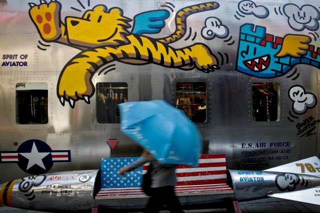 A woman walks by a bench painted with an American flag outside a fashion boutique selling U.S. brand clothing at the capital city