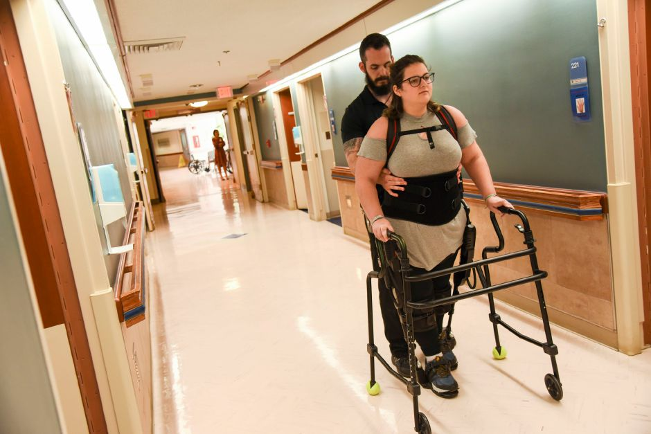 Carbaugh walks down a hospital wing during an outpatient therapy session. session.Gaylord Speciality Healthcare in Wallingford on Sept. 13, 2019. Physical therapist Tim Kilbride provides support. | Bailey Wright, Record-Journal
