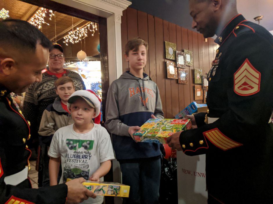 U.S. Marines First Sgt. Efren Casas accepts a toy from John Fryer, 9, of Wallingford Thursday night during the annual Toys for Tots toy Drive at Gaetano