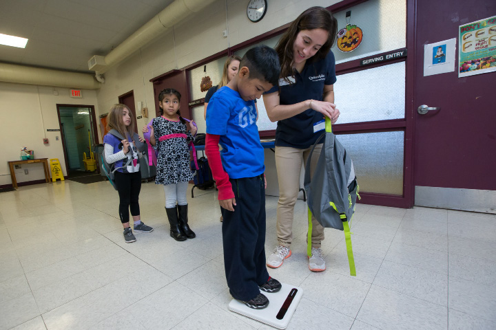 Noe Galvez 7 steps on a scale to compare his weight without his backpack with  occupational therapy student Taylor Miller of Quinnipiac University Tuesday during a Backpack Safety Program at Evarts C. Stevens Elementary School in Wallingford. Students learned that the backpack should not be more than ten percent of their body weight. Nov. 1, 2016 | Justin Weekes / For the Record-Journal