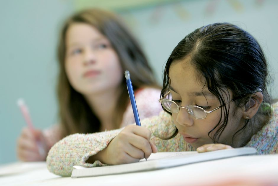 Record Journal Photo/ Johnathon Henninger 10.05.09 - Katzumy Berru Sanmartin, 9, right, writes down notes as she learns the French language with classmate, Catrina Gadwah-Meaden, 11 from Melissa Dion, who is teaching French at Girls Inc. in Meriden Monday afternoon.