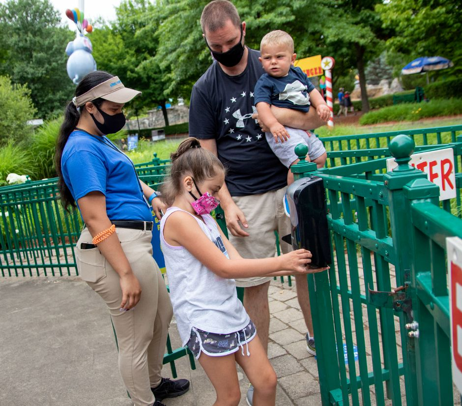 Kiddie Carousel attendant Nayelie Arroyo, left,  looks on as  Isabella Czarnecke, 7, cleans her hands alongside   her father, Jason Czarnecke, as he holds Isabella's 13-month-old brother,   Jason. The family is from Wolcott.