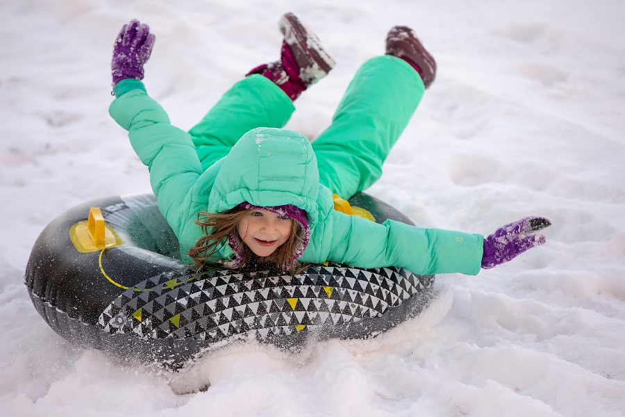 Seven-year-old Cassidy O'Brien,  of Meriden, tubes down a snowy hill in the front yard of her Baldwin Avenue residence on Wednesday. Cassidy and brother Jack, 9, enjoyed the day off from Nathan Hale School. Dave Zajac, Record-Journal