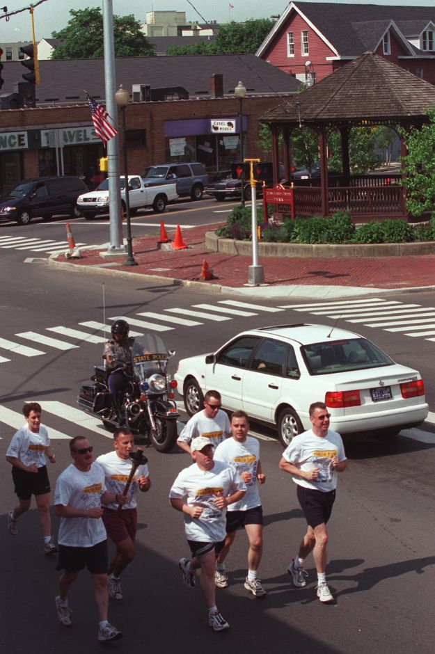 Wallingford police officers participate in the annual torch run for the Special Olympics. They are crossing the intersection of Center Street and North Colony in Wallingford Thursday June 8, 2000.