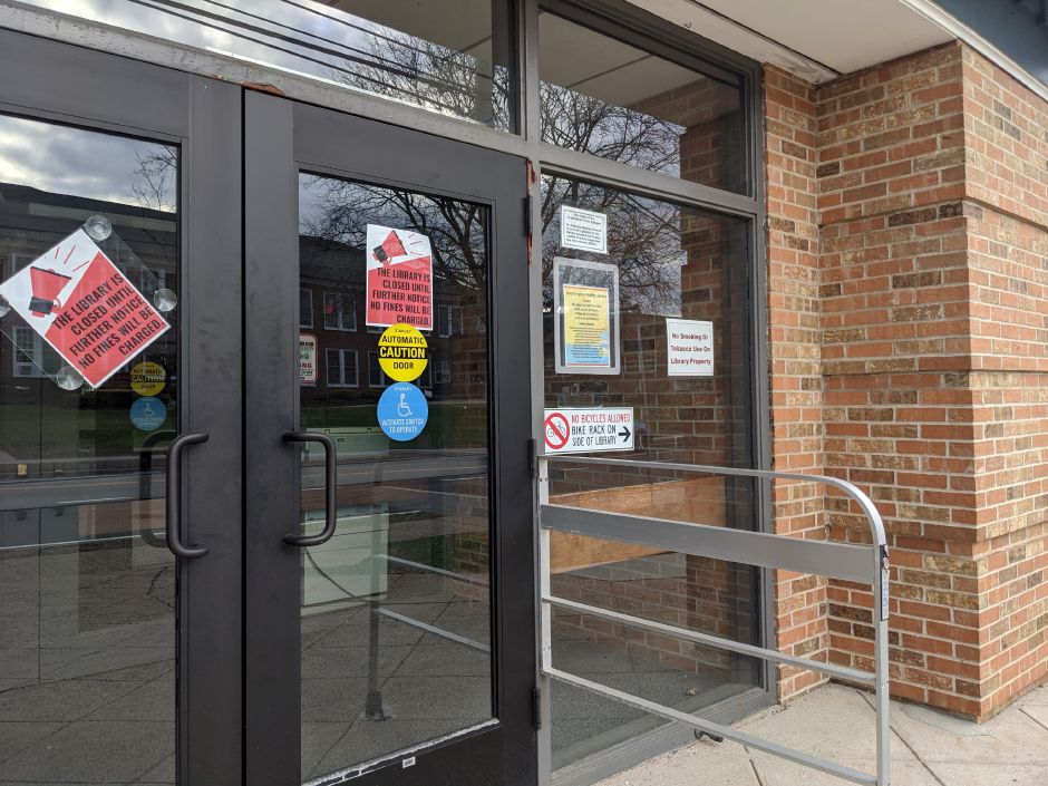 Signs hang on the doors of the Southington Public Library, informing patrons that the library