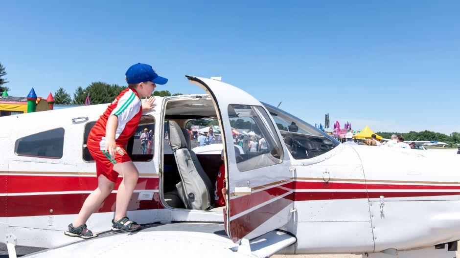 Gabriel Omilian climbs into the cockpit of a Piper PA-28 on display during the Wings and Wheels car and air show at Robertson Airport in Plainville on June 8, 2019. | Devin Leith-Yessian/Plainville Citizen