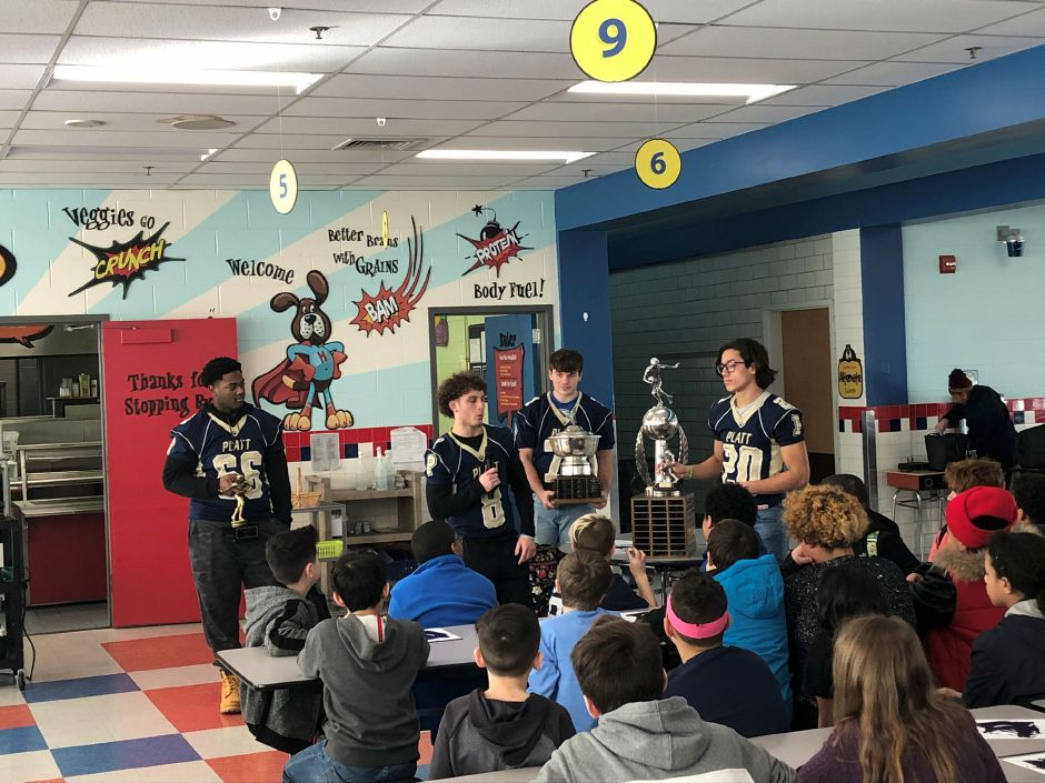 From left, Platt football players Jaylen John, Jake Baker, Daniel Hand and Roberto Salas address Hanover Elementary School fourth- and fifth-graders in Meriden on Tuesday afternoon. The visit was part of a tour the Platt football program has been making of the city's elementary schools to promote high school students as role models for younger students. Sean Krofssik, Record-Journal