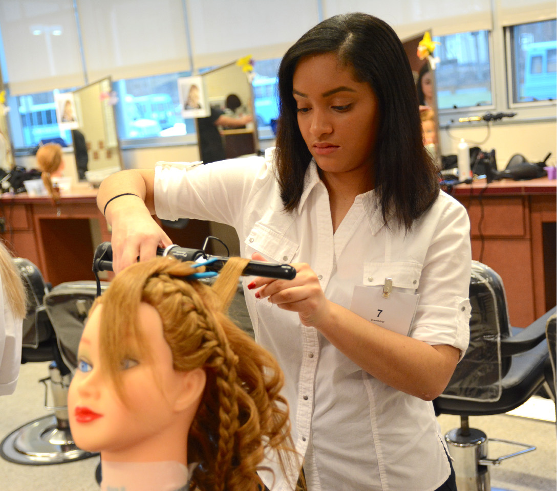 Nataly Pena, of Grasso Technical High School, creates an updo hairstyle during a Skills USA competition at Wilcox Technical High School on Friday, March 31, 2017. | Bryan Lipiner, Record-Journal