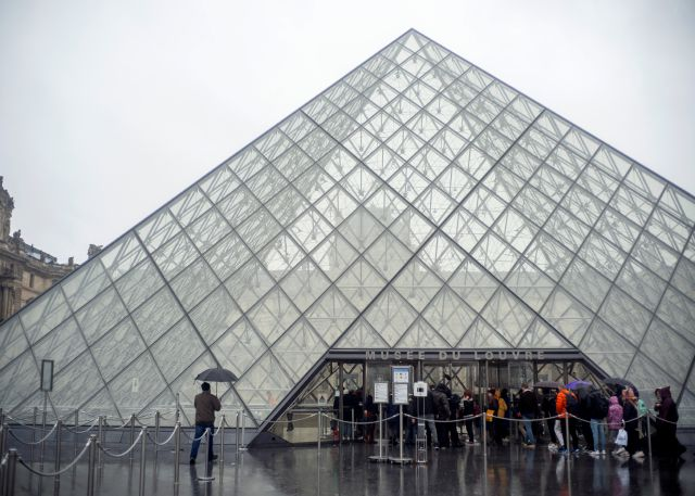 Tourists stand outside the Louvre museum, in Paris, France, Sunday, March 1, 2020. The spreading coronavirus epidemic shut down France