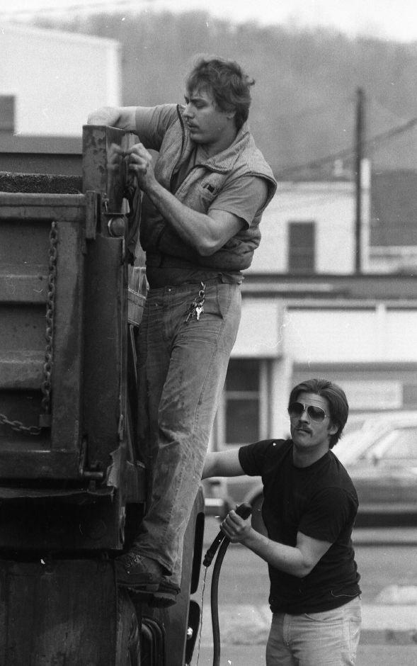 RJ file photo - Grant Williams and Jay Agli take advantage of the unseasonably warm temperatures to give a paving truck a good wash. Williams is the owner of Williams Paving in Wallingford, Feb. 1989.