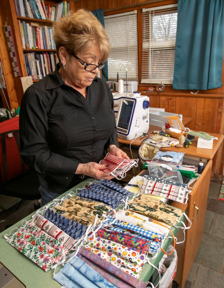 Patricia Longobardi, owner of Sewing by Patricia in Wallingford, looks over a variety of fabric masks she