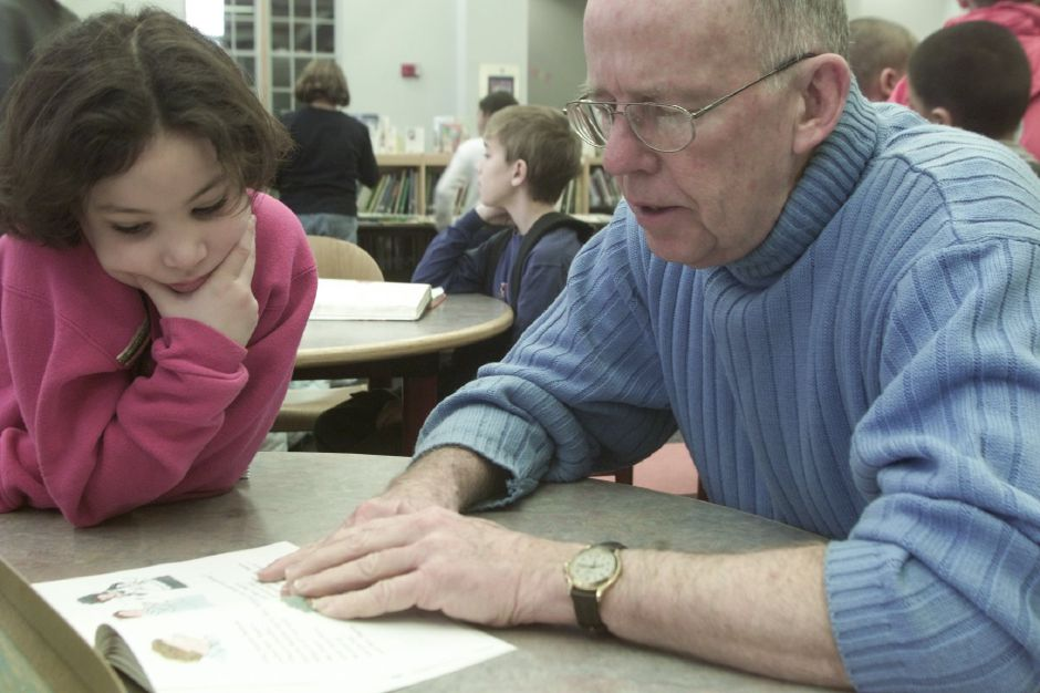 Ned Roesler, volunteers his time , with second grader Katie Caro,7, during the Early Start program at John Barry Elementary School on Tuesday Jan 16, 2001. Volunteers and staff from the Family resource Center help the 50 or so children that take advantage of the early morning program. Volunteers are available to help with school work including math and reading.