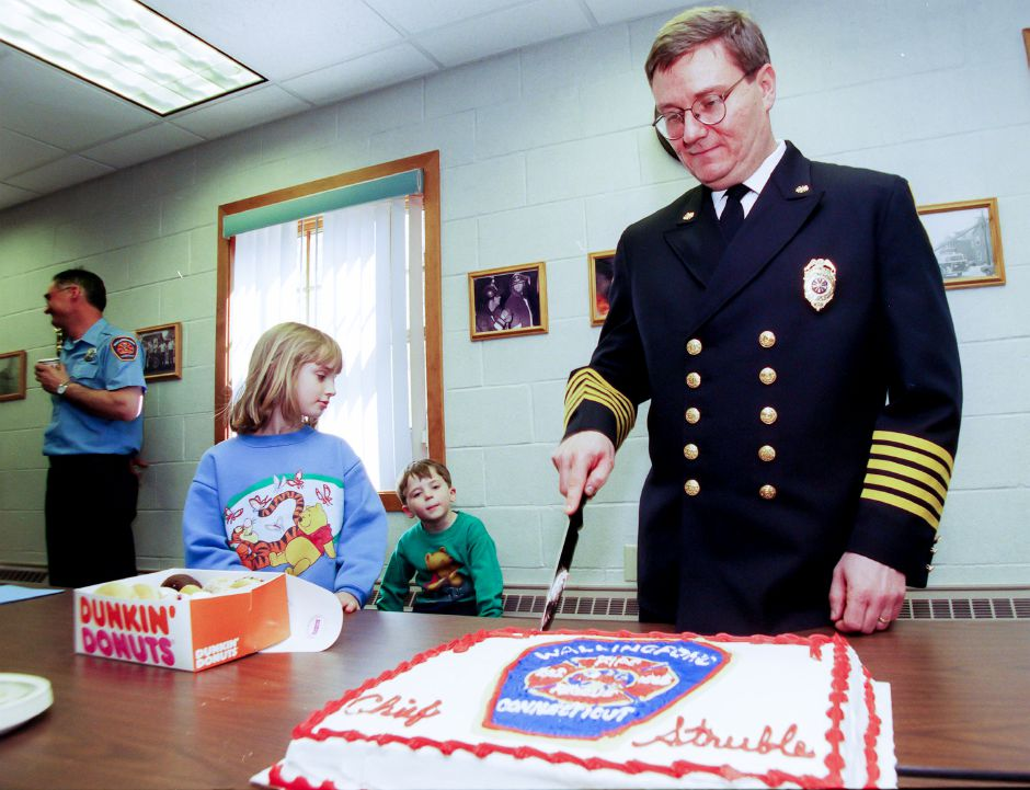 Wallingford Fire Department Chief Peter Struble cuts a cake made for him shortly after being sworn in to his new position by Wallingford Mayor William Dickenson at Fire Headquarters in Wallingford Friday April 14, 2000. On the left is his daughter Danielle Struble, 8, and son Matthew, 5.