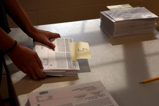 A volunteer sorts mail-in ballots on Primary Day, Tuesday, Aug. 11, 2020, in Glastonbury, Conn. (AP Photo/Jessica Hill)