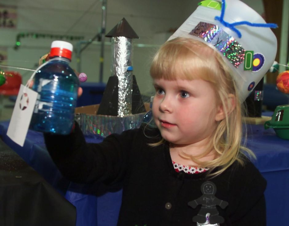 Emily Flynn, 3 and 1/2, models the space hat she made and loks at a bottle of glitter water at the Girls, Inc. pre-school art show Thurs., March 16, 2000.