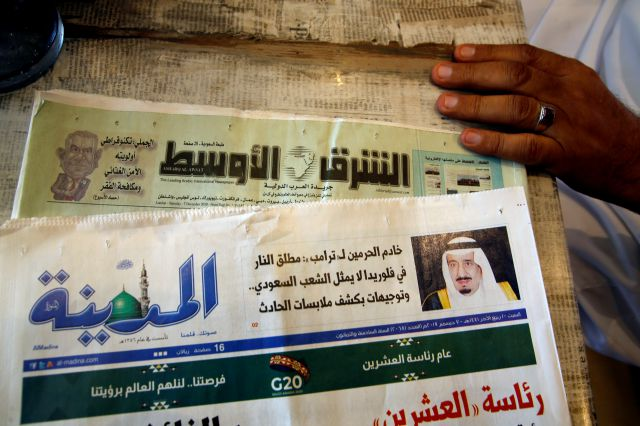 Saudi daily Al-Madina newspaper fronted by a picture of Saudi King Salman is displayed at a coffee shop in Jiddah, Saudi Arabia, Saturday, Dec. 7, 2019. U.S. law enforcement officials were digging into the background of the suspected Florida naval station shooter Friday, to determine the Saudi Air Force officer