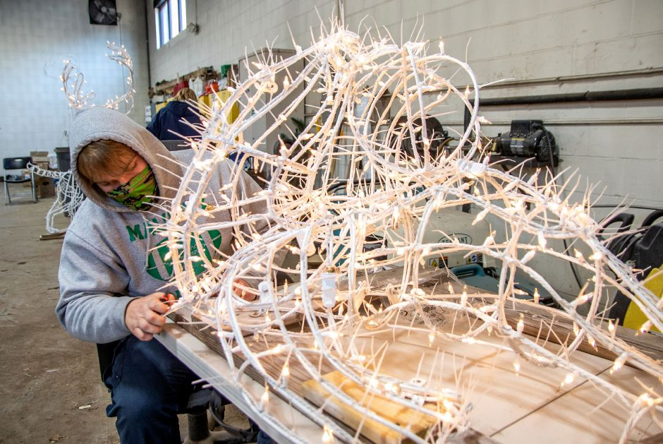 Meriden Park and Recreation's Elijah Manke works on restringing one of the seals that are used for the Festival of Silver Lights at Hubbard Park in Meriden. Aaron Flaum, Record-Journal