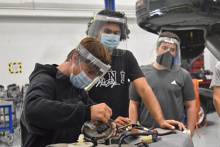 John Bell works to remove a fuel pump during class at Gateway Community College in North Haven.