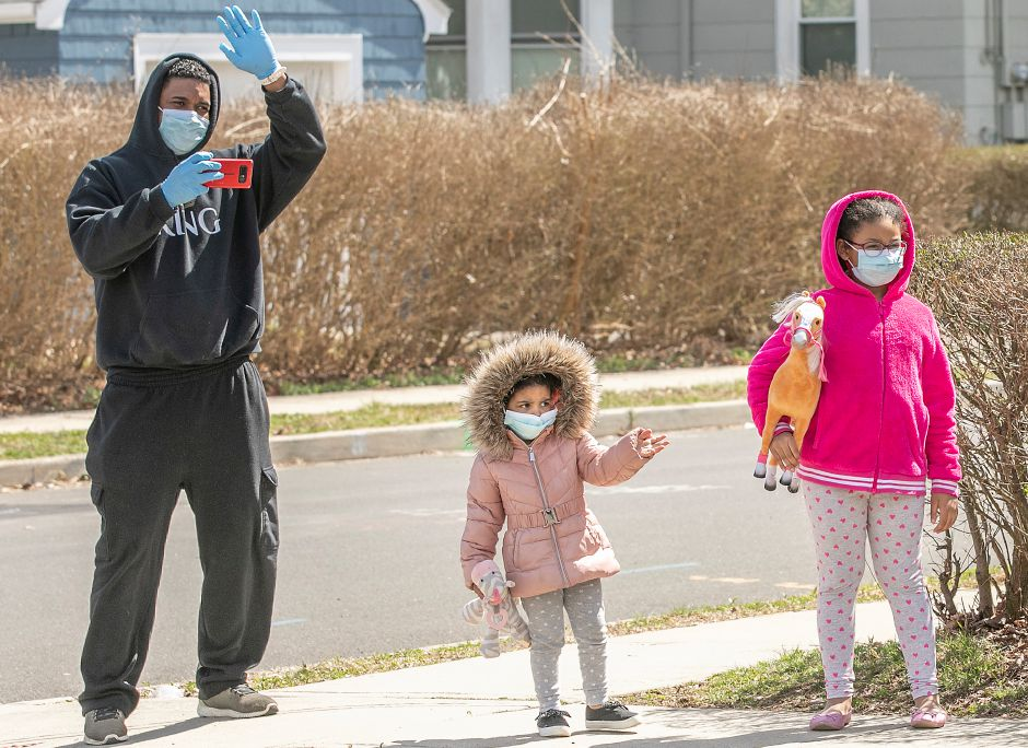 Edgar Diaz, of Meriden, and daughters Valentina, 3, and Melanie, 8, wave to teachers during Casimir Pulaski Elementary School