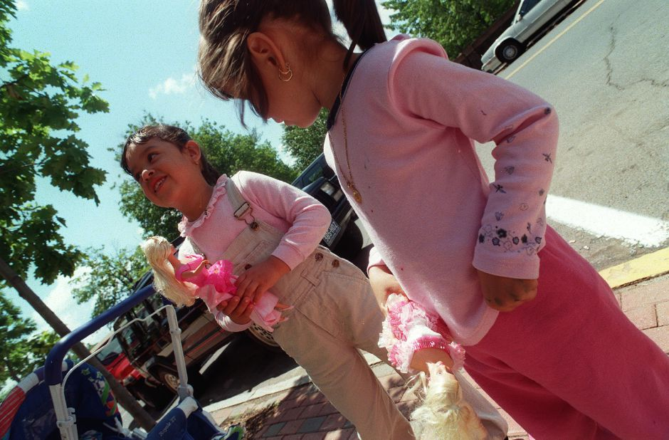 Jessica, left, and Lupita Solis, right, take their barbie dolls for a stroll down Hall Street in Wallingford, Wednesday afternoon June 7, 2000.